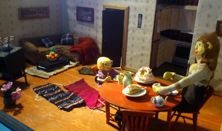 Så här hade vi ställt upp ett par kulisser inför semesterevalueringen. Gud och Anne festande på tårta vid matbordet. Tv soffa och dörr till Guds rum och kök i bakgrunden.